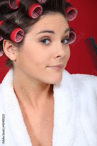 Young woman wearing hair curlers