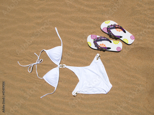Bikini and flip-flops on the sand