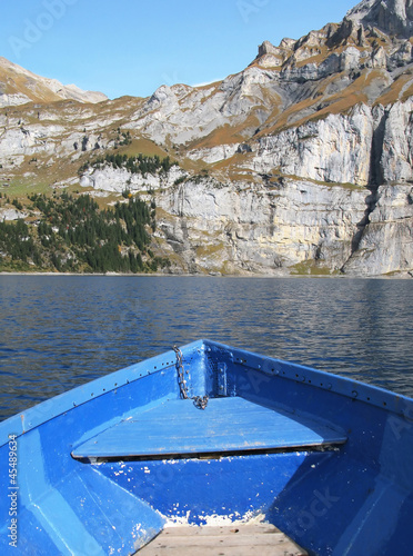 Prow of a boat against surface of Oeschinensee lake and Alps
