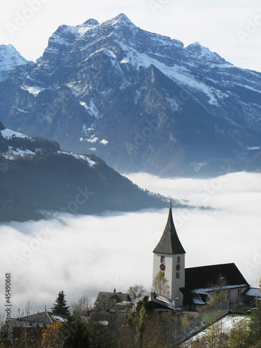 Rural church in Amden against snowy Alps, Switzerland