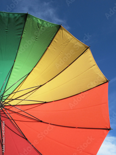 Spectrum colored umbrella against blue sky