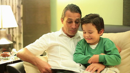 father and son reading a book