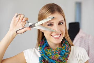 Frau mit Schneiderschere vor Gesicht