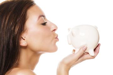 schöne junge frau küsst sparschwein vor weissem hintergrund
