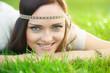 Smiling hippie girl on green grass