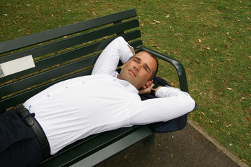 Smartly dressed man resting on a park bench
