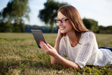 Young woman reading e-book in nature