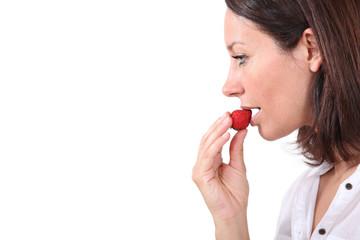 Brunette eating strawberry