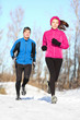 Young couple jogging in winter snow