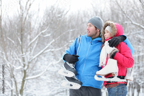 Young couple carrying ice skates