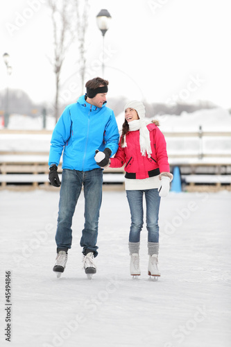 Young couple ice skating outdoors