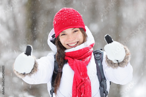 Happy woman in snowstorm giving thumbs up