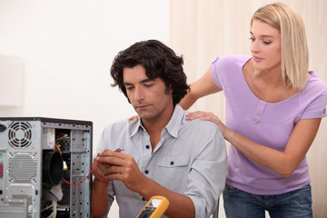 Technician repairing PC for attractive colleague