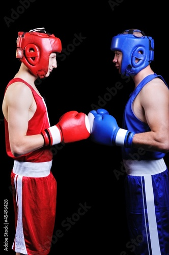Two male boxers fighting on black background