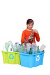 Young girl recycling plastic bottles and batteries