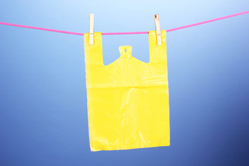 Cellophane bag hanging on rope on blue background