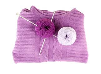 Purple sweater and a ball of wool isolated on white