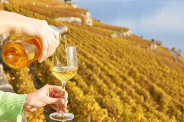 Filling up a wineglass against vineyards in Lavaux region, Switz