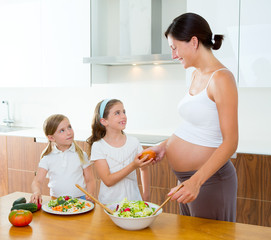 Beautiful pregnant mother with her daughters at kitchen