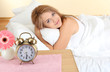 young beautiful woman lying on bed with alarm clock in bedroom