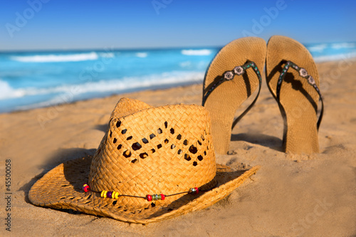 golden sand beach with summer hat and sandals