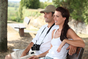 Couple with camera sat on bench