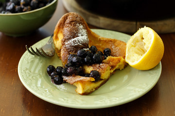 A slice of dutch baby pancake served with blueberry sauce