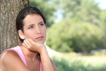 Pensive woman with tree trunk