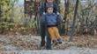 Mom Pushing her son on a swing in a park in autumn