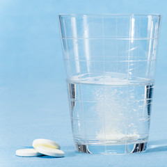 Fizzy vitamin capsule throw in water glass