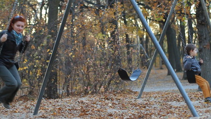 Mom and son ride on a swing in a park in autumn