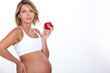 A pregnant woman eating an apple.