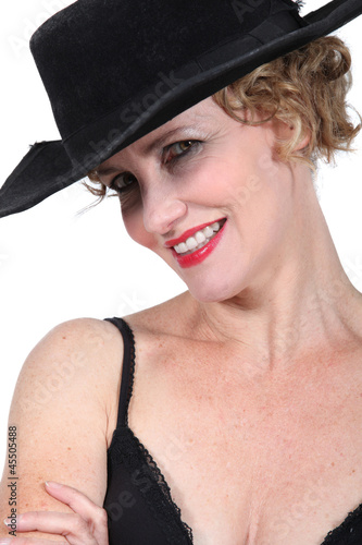 Smiling woman in black hat and bra
