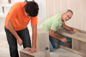 Father and son putting together flat pack furniture