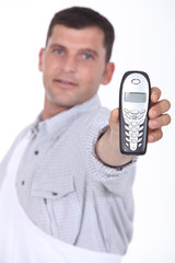Man holding out mobile telephone