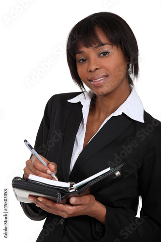 An African American businesswoman with a planner.