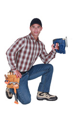 craftsman kneeling and holding a drill