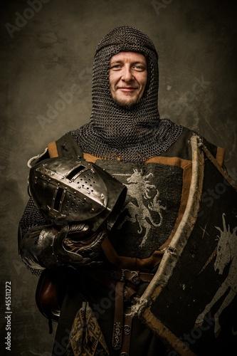 Smiling medieval knight  holding helmet