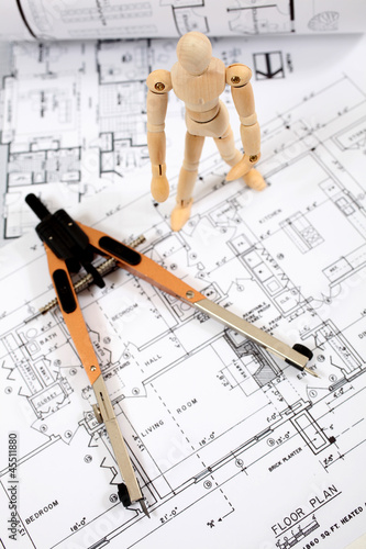Maniking standing on building plans equipped with measuring tool