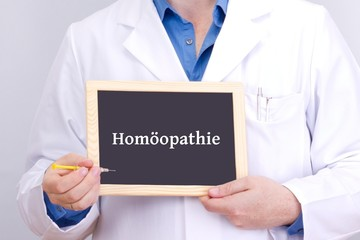 Doctor shows information on blackboard: homeopathy