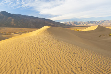 desert sand dunes with mountain in the background