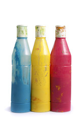 three dirty paint cans, blue yellow and pink, isolated