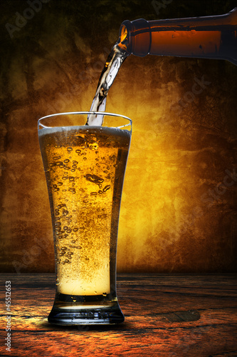 beer pouring from beer bottle to glass
