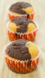 A row of chocolate and vanilla muffins on a wooden background