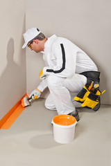 worker brush waterproofing around the wall and floor