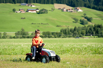 Kid playing with tractor toy outdoors.