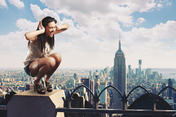 Beautiful girl listening to music standing on the rooftop