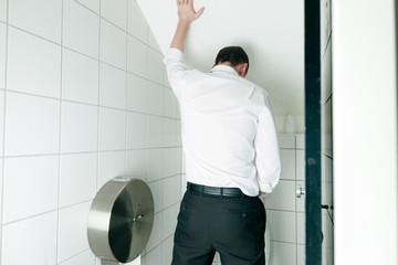 Ein Mann steht in der Toilette und pinkelt