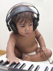neonato con cuffie che suona la tastiera