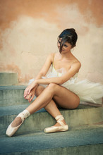 Young beautiful ballerina posing sit on the stairs.